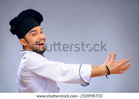 Grasping copy space. Side view portrait of laughing handsome cook trying to catch copy space while standing against grey background with copy space - stock photo