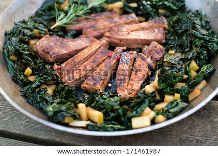 Grass Fed Beef Steak Seared and Sliced Served with Wilted Kale on Stainless Steel Skillet - stock photo