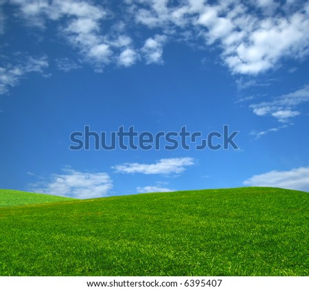 Grass Hill with bright blue sky - stock photo