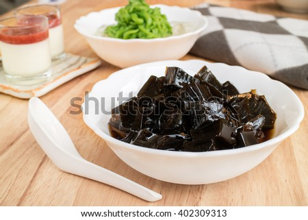 Grass Jelly dessert herbal gelatin with syrup, ice, and brown sugar on top in vintage tone - halal dessert - stock photo