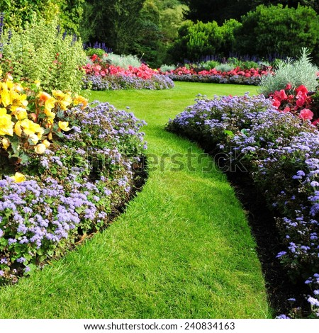 Grass Path and Flowerbed in a Beautiful Garden - stock photo