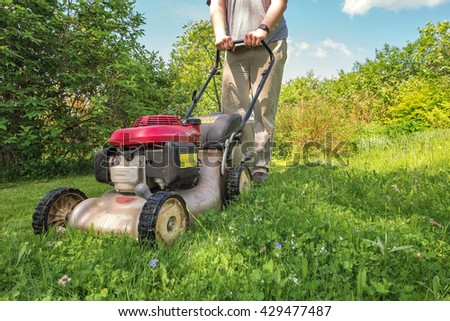 Grass trimming with lawnmower. Gardening. - stock photo