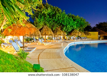 Grass umbrella with lounges at a swimming pool at a caribbean resort at night, dawn time - stock photo