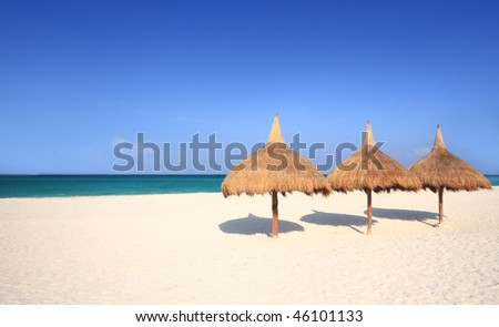 Grass umbrellas at a beach resort - stock photo