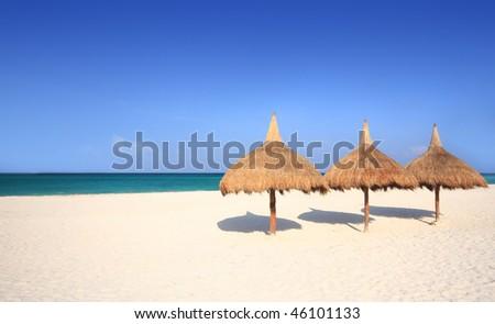 Grass umbrellas at a beach resort - stock photo