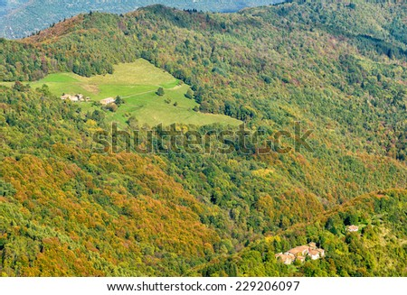 grassland, colorful forest and small villages on hills in fall, Ariege, France - stock photo