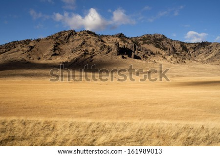 Grassland leads up to rocky mountain hillside in this northern rural landscape - stock photo