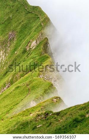 Grassy ridge with fog. - stock photo
