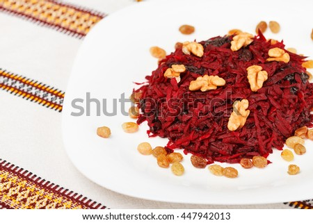 Grated beet salad with prunes, raisins and walnut served on a white plate and home tablecloth. low aperture shot, selective focus - stock photo