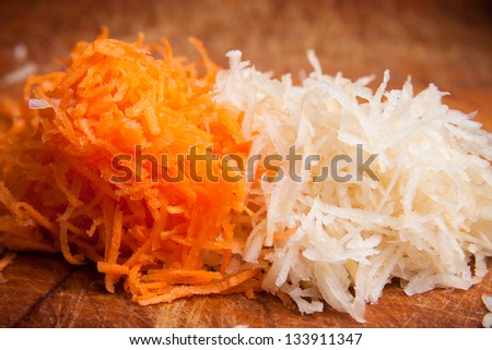 Grated carrot and celery wooden plate - stock photo