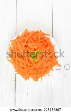 Grated carrot in bowl on white wooden table, top view - stock photo