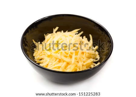 Grated cheddar cheese in a black bowl, isolated on white. - stock photo