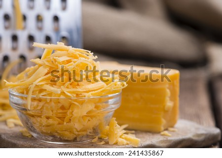 Grated Cheddar Cheese in a small bowl on rustic wooden background - stock photo