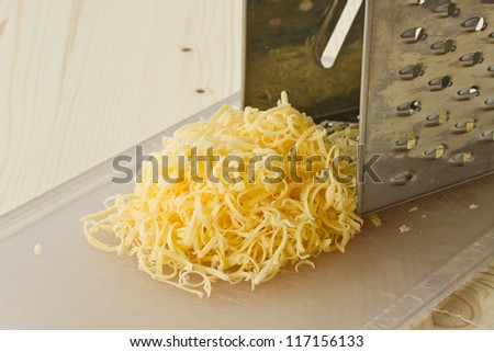 grated cheese on the board near the float - stock photo