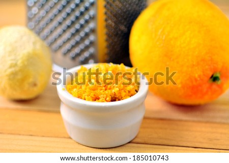 Grated citrus (orange and lemon) rind and grater. - stock photo