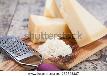 grated parmesan cheese and metal grater on wooden board - stock photo