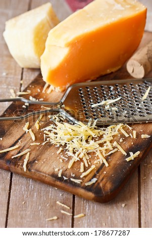 Grated parmesan cheese with a grater close-up. - stock photo