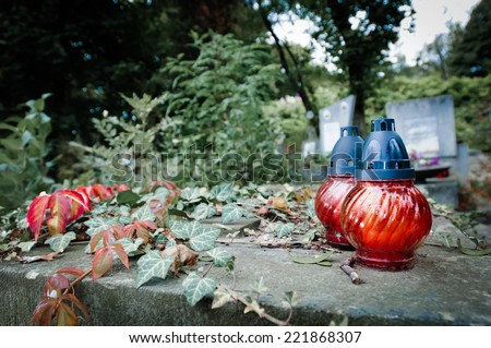Grave in twitlight with ivy and red icon lamp - stock photo