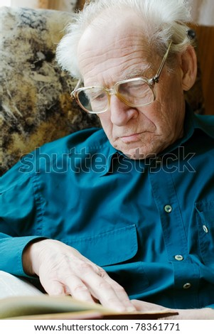 grave old man in glasses reading a book - stock photo