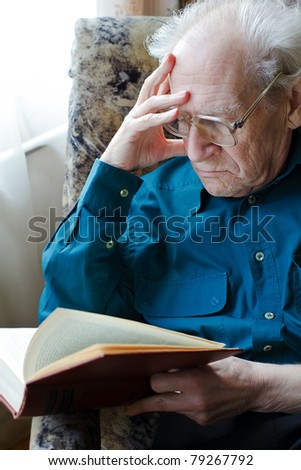 grave old man in glasses reading a book, holding his head - stock photo
