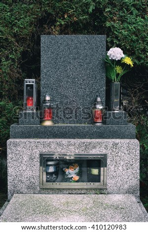 Grave with urn, flowers and candles. Bush in the background. Symbol of mortality and death. Free copy space for your own text - epitaph - on gravestone  - stock photo