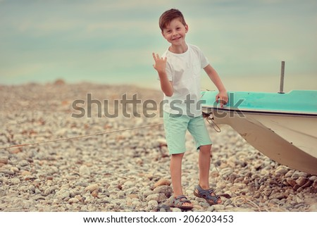 gravel on the sea worth cheerful cute little boy and the boat - stock photo