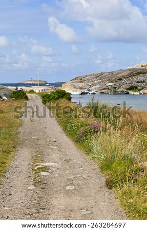 Gravel road over the meadows to the sea - stock photo