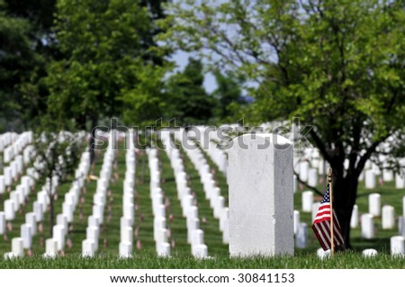 Gravestones decorated with U.S. flags to commemorate Memorial Day at the Arlington National Cemetery in Arlington, Virginia. One gravestone in the foreground with copyspace. Narrow DOF. - stock photo