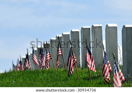 Gravestones decorated with U.S. flags to commemorate Memorial Day at the Arlington National Cemetery in Arlington, Virginia, near Washington DC. Narrow DOF. - stock photo