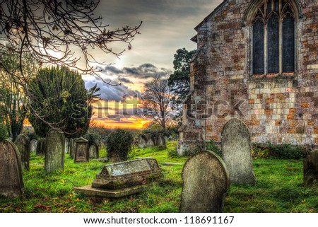 Graveyard at sunset with church - stock photo