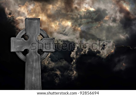 Graveyard cross against dramatic storm clouds - stock photo