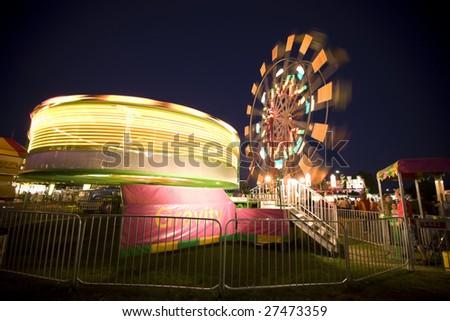 Gravity Machine with Ferris Wheel in Background - stock photo