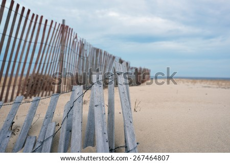 Gray and weathered storm fence slowly being covered by sand dunes - stock photo