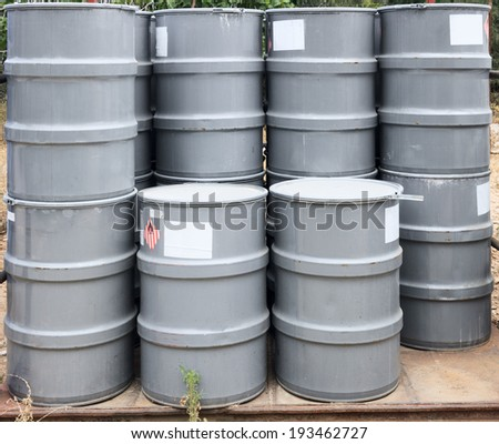 Gray barrels on a chemical plant - stock photo