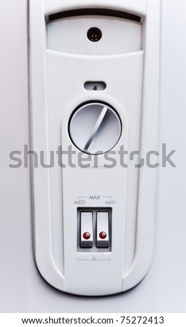 gray electric oil heater control panel with switches - stock photo