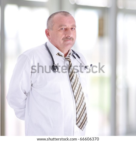 gray hair expertise handsome senior doctor hospital portrait white corridor - stock photo