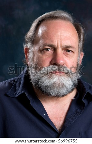 Gray haired bearded man has a serious and somber look. - stock photo