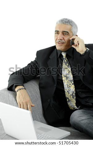 Gray haired businessman sitting on sofa with laptop computer, talking on mobile phone, smiling. - stock photo