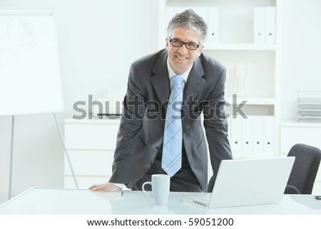 Gray haired executive businessman working on laptop computer at desk, in office. - stock photo