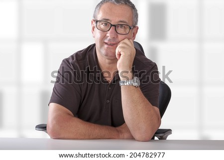 Gray-haired man with glasses sitting at desk - stock photo