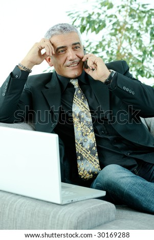 Gray haired mature businessman sitting on couch working on laptop computertalking on mobile phone, happy, smiling. - stock photo