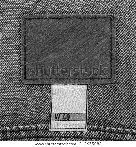 gray leather label on black jeans background  - stock photo