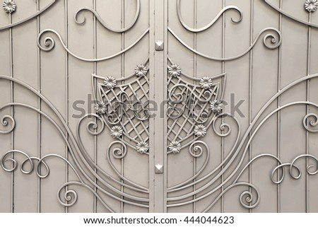 gray metal door with forging. n the gate depicts the initials A, T - stock photo