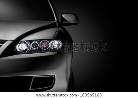 Gray modern car closeup on black background. - stock photo
