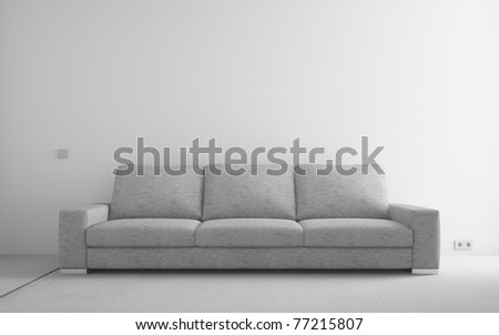 Gray modern sofa in empty room with white walls and concrete floor - stock photo