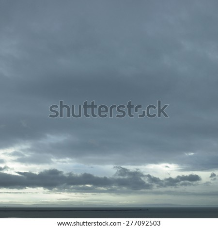 Gray ocean water with a silhoutted spit of land with a huge sky above - stock photo