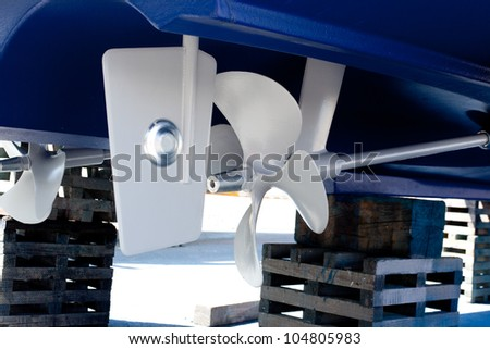 gray painted propeller and steering with zinc anodes in blue hull - stock photo