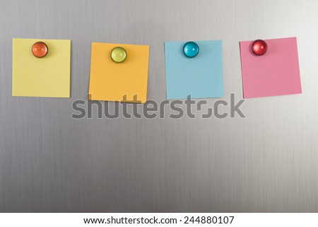 Gray Refrigerator Door With Colorful Notes Posted With Magnets - stock photo