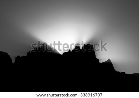 gray scale sunset behind mountain peak - stock photo