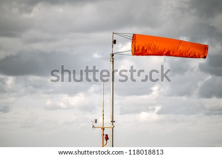 Gray steel sky before storm with fire-red airsock and signal light - stock photo